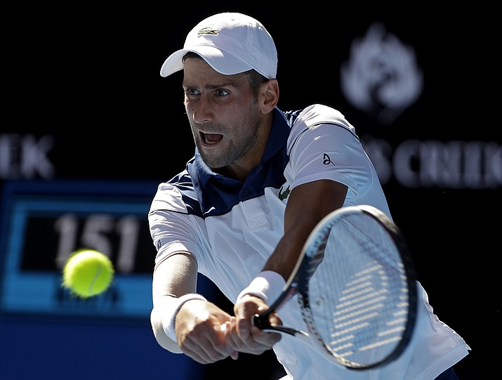 Serbia's Novak Djokovic makes a backhand return to United States' Donald Young during their first round match at the Australian Open on Tuesday, Jan. 16, 2018, in Melbourne, Australia. (Dita Alangkara/AP)