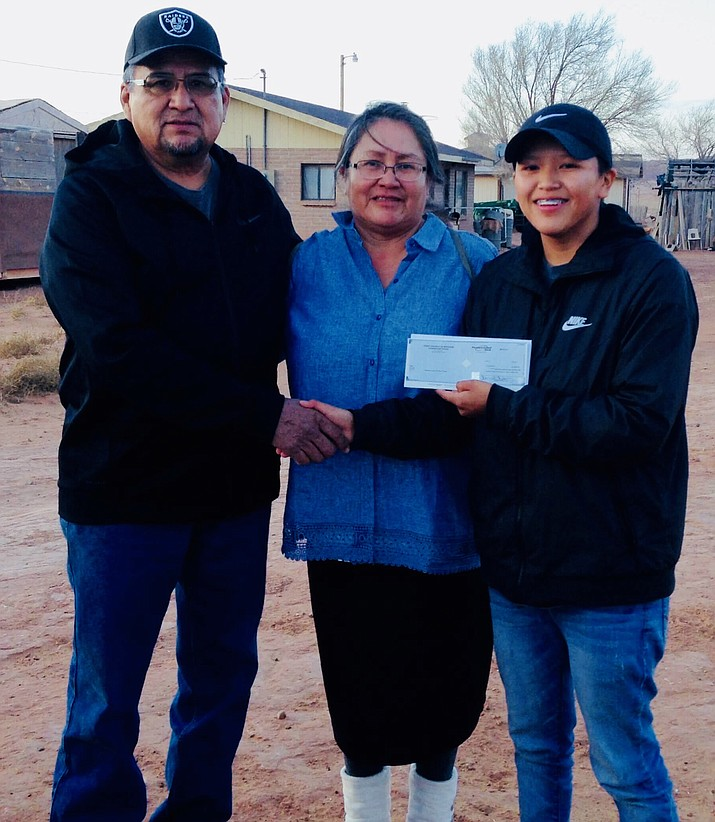 Kayenta Chapter President Stanley Clitso (left) presents Darrien Clitso (right) the Lauren Swisher Memorial Scholarship Dec. 25.  Becky Clitso (center) was present when her daughter accepted the scholarship.