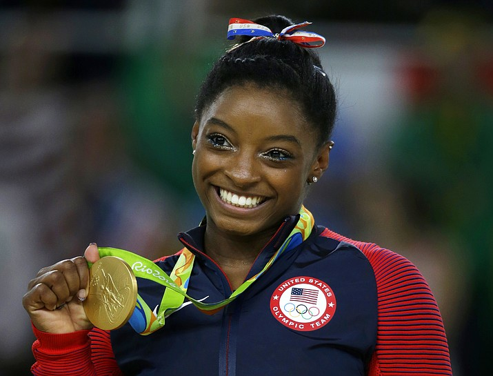 In this Aug. 16, 2016 file photo, United States gymnast Simone Biles displays her gold medal for floor during the artistic gymnastics women's apparatus final at the 2016 Summer Olympics in Rio de Janeiro, Brazil. (Rebecca Blackwell/AP, File)