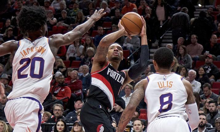 Portland Trail Blazers guard Damian Lillard, center, shoots over Phoenix Suns forward Josh Jackson, left, and Phoenix Suns guard Tyler Ulis, right, during the first half Tuesday, Jan. 16, 2018, in Portland, Ore. (Craig Mitchelldyer/AP)