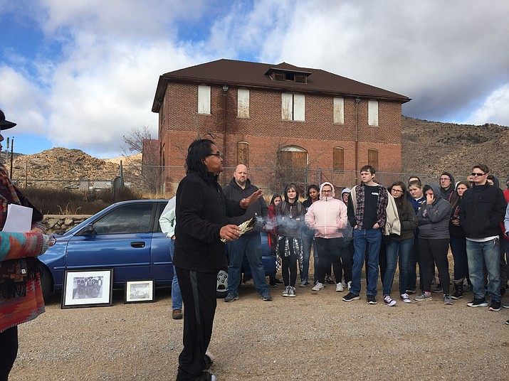 Hualapai Elder Drake Havatone burns sage in front of the Truxton Canyon Training School and explains to Lee Williams students the significance of the sage burning ceremony.