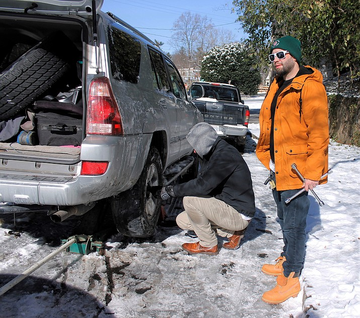Brandon Lemasters, standing, helps a friend change a tire on his SUV on Thursday, Jan. 18, 2018, in Winston-Salem, after the vehicle slid through a curve on a ice-covered street the day before and hit a curb. North Carolina and other Southern states spent Thursday digging out from a snow storm. (AP Photo/Skip Foreman)