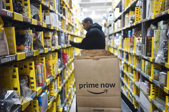 A clerk reaches to a shelf to pick an item for a customer order at the Amazon Prime warehouse, in New York. Amazon announced Thursday, Jan. 18, 2018, that it has narrowed down its potential site for a second headquarters in North America to 20 metropolitan areas, mainly on the East Coast. (AP Photo/Mark Lennihan, File)