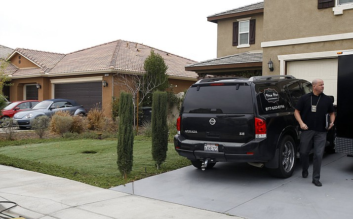 Detective walks next to a home Tuesday, Jan. 16, 2018, where police arrested a couple on Sunday accused of holding 13 children captive, in Perris, Calif.  (AP Photo/Alex Gallardo)