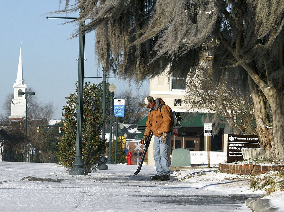 Rickey Ranger, with the Craven County Maintenance Department, works to clear snow at Craven County administrative buildings on Broad Street in New Bern, N.C., Thursday, Jan. 18, 2018, after a winter front brought frigid weather across the region overnight. (Gray Whitley/Sun Journal via AP)