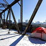A tent sits in the snow on a bridge frequented by the homeless as the downtown skyline stands in the background in Atlanta, Thursday, Jan. 18, 2018. The deep freeze that shut down much of the South began to relent Thursday as crews worked to clear roads blanketed by a slow-moving storm that left ice and snow in places that usually enjoy mild winters. (AP Photo/David Goldman)
