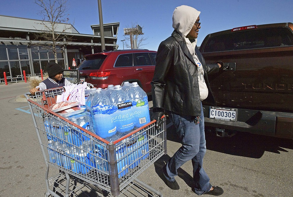 Mid-city resident Dianne Mason, right, brings a shopping cart full of water, pushed by her great-grandson Treyvon Tillery, left, to her truck at Costco in New Orleans, Thursday, Jan. 18, 2018. The winter blast that brought unusually cold weather to south Louisiana is causing serious problems for some water systems, with officials in St. John the Baptist Parish calling on residents Thursday to immediately stop using tap water. (Max Becherer /The Advocate via AP)