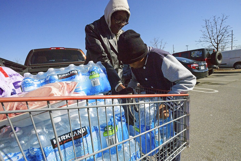 Mid-city resident Dianne Mason, right, brings a shopping cart full of water, pushed by her great grandson Treyvon Tillery, left, to her truck at Costco in New Orleans, Thursday, Jan. 18, 2018. The winter blast that brought unusually cold weather to south Louisiana is causing serious problems for some water systems, with officials in St. John the Baptist Parish calling on residents Thursday to immediately stop using tap water. (Max Becherer /The Advocate via AP)