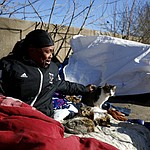 """Larry Gilliam sits with cats who keeps him company along a bridge frequented by the homeless where he sleeps in Atlanta, Thursday, Jan. 18, 2018. """"I can't say it won't happen to me but I hope for the best and prepare for the worst,"""" said Gilliam about reports that homeless people had died from hypothermia in the recent cold temperatures. The deep freeze that killed more than a dozen people and shut down much of the South began to relent Thursday as crews worked to clear roads blanketed by a slow-moving storm that left ice and snow in places that usually enjoy mild winters. (AP Photo/David Goldman)"""