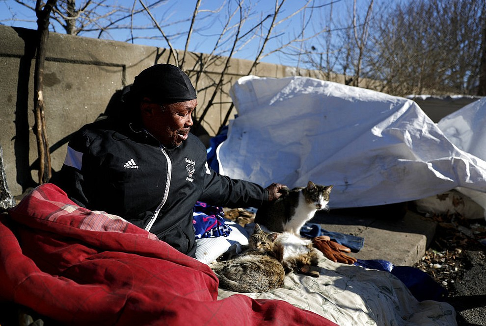 "Larry Gilliam sits with cats who keeps him company along a bridge frequented by the homeless where he sleeps in Atlanta, Thursday, Jan. 18, 2018. ""I can't say it won't happen to me but I hope for the best and prepare for the worst,"" said Gilliam about reports that homeless people had died from hypothermia in the recent cold temperatures. The deep freeze that killed more than a dozen people and shut down much of the South began to relent Thursday as crews worked to clear roads blanketed by a slow-moving storm that left ice and snow in places that usually enjoy mild winters. (AP Photo/David Goldman)"