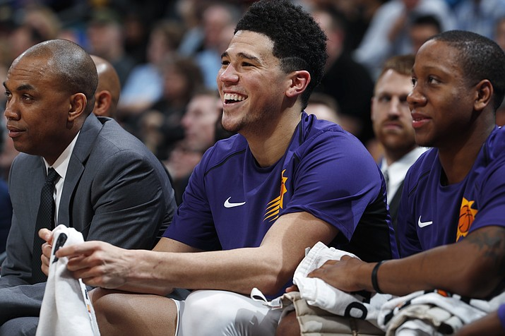 Phoenix Suns guard Devin Booker, center, laughs as fans heckle him and Phoenix Suns guard Isaiah Canaan, right, during the second half of the team's game against the Denver Nuggets on Friday, Jan. 19, 2018, in Denver. Phoenix won 108-100. (David Zalubowski/AP)