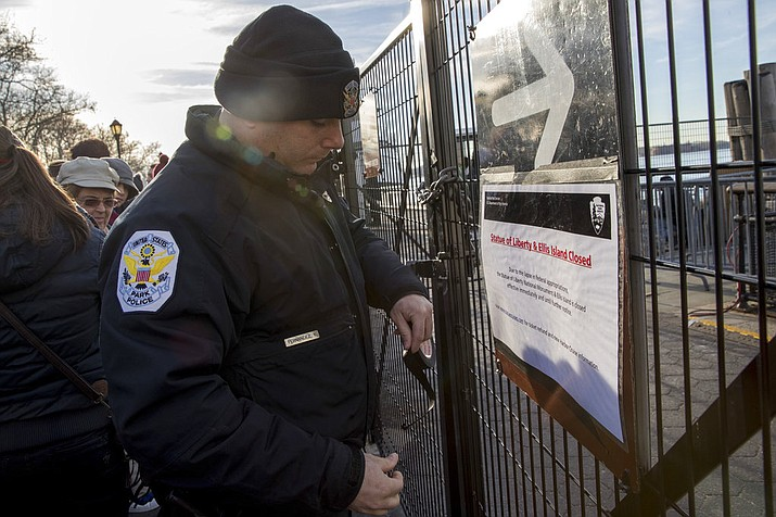 """A United States Park Police officer post a sign informing of the Statue of Liberty and Ellis Island closing at an entrance to the ferry, Saturday, Jan. 20, 2018, in New York. The National Park Service announced that the Statue of Liberty and Ellis Island would be closed Saturday """"due to a lapse in appropriations."""" (AP Photo/Mary Altaffer)"""