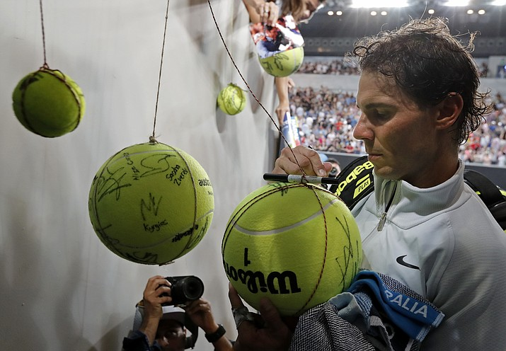 Spain's Rafael Nadal signs autographs after defeating Damir Dzumhur of Bosnia and Herzegovina in their third round match at the Australian Open tennis championships in Melbourne, Australia, Friday, Jan. 19, 2018. (Vincent Thian/AP)