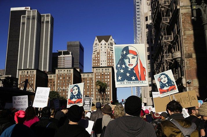 People gather for a Women's March, Saturday, Jan. 20, 2018, in Los Angeles. On the anniversary of President Donald Trump's inauguration, people participating in rallies and marches in the U.S. and around the world Saturday denounced his views on immigration, abortion, LGBT rights, women's rights and more. (AP Photo/Jae C. Hong)