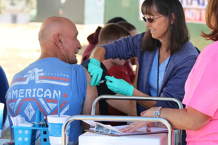 Rose Tena, a registered nurse, gives a flu shot to a veteran at the Veterans Olympic Day. (Courtesy)