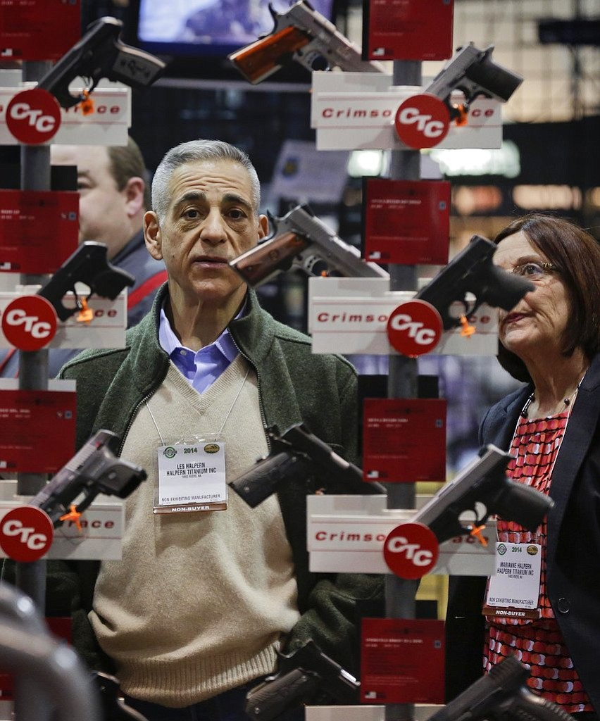 FILE - In this Jan. 14, 2014, file photo, knife manufacturers Les Halpern, left, and Marianne Halpern, of Three Rivers, Mass., examine a display of various handguns outfitted with laser sights on display at the Crimson Trace exhibit during the Shooting Hunting and Outdoor Trade Show in Las Vegas. The largest gun industry trade show will be taking place in Las Vegas Jan. 23-26 just a few miles from where a gunman carried out the deadliest mass shooting in modern U.S. history. (AP Photo/Julie Jacobson, file)