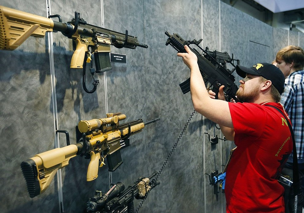 FILE--In this Jan. 19, 2016 file photo, Nolan Hammer looks at a gun at the Heckler & Koch booth at the Shooting, Hunting and Outdoor Trade Show in Las Vegas. The largest gun industry trade show will be taking place in Las Vegas Jan. 23-26 just a few miles from where a gunman carried out the deadliest mass shooting in modern U.S. history. (AP Photo/John Locher, File)