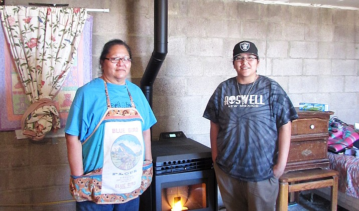 Carolyn Lomabalaquihoya and her daughter, Tierra, stand in front of the new pellet stove installed by Roof Dancers and Red Feather Development Group Jan. 19.