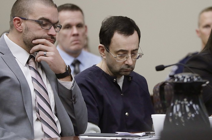 """Larry Nassar sits with attorney Matt Newburg during his sentencing hearing Wednesday, Jan. 24, 2018, in Lansing, Mich. The former sports doctor who admitted molesting some of the nation's top gymnasts for years was sentenced Wednesday to 40 to 175 years in prison as the judge declared: """"I just signed your death warrant."""" The sentence capped a remarkable seven-day hearing in which scores of Nassar's victims were able to confront him face to face in the Michigan courtroom. (AP Photo/Carlos Osorio)"""