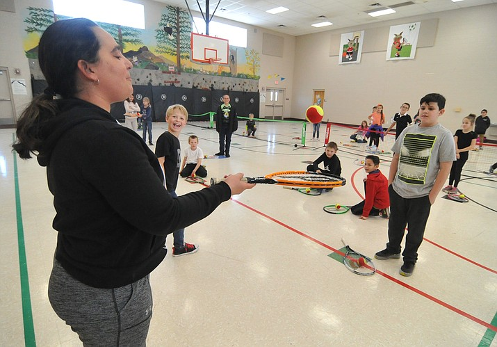 Melissa Bates, a teacher at Taylor Hicks Elementary School in Prescott, demonstrates a tennis skill during 4th grade physical education class Monday morning.