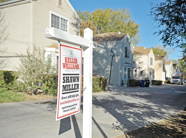 A real estate sign sits in front of a group of homes in this photo from 2014. (Courier file photo)