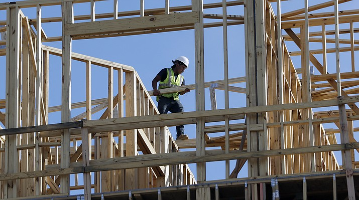 In this Friday, Oct. 6, 2017, photo, workers build an apartment and retail complex in Nashville, Tenn. On Friday, Jan. 26, 2018, the Commerce Department issues the first estimate of how the U.S. economy performed in the October-December quarter. (AP Photo/Mark Humphrey)