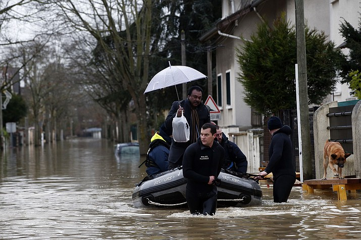 Rescue workers evacuate residents in a flooded street of Villeneuve-Saint-Georges, outside Paris, where the Yerres river floods Thursday, Jan.25, 2018. Rivers across France kept swelling as more rain hit the country Thursday, with 15 departments across the country remaining on alert for floods. In addition to Paris, where the Seine river is expected to keep rising until Saturday, the other regions threatened are in the north and east of the country. (AP Photo/Christophe Ena)