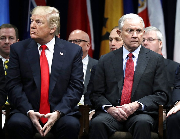 In this Dec. 15, 2017, file photo, President Donald Trump and Attorney General Jeff Sessions attend the FBI National Academy graduation ceremony in Quantico, Va. Sessions will soon mark his first year as the nation's chief law enforcement officer. That comes even after a year that included a barrage of insults from President Donald Trump, antipathy from some of his own employees and even some calls from his fellow Republicans to resign. (AP Photo/Evan Vucci, File)
