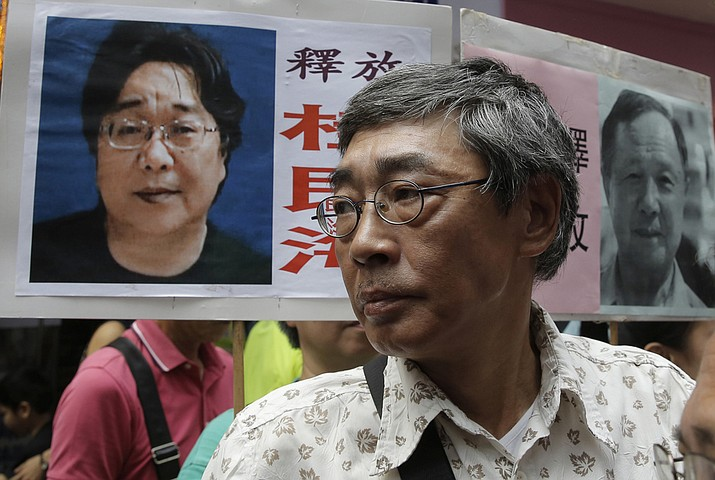 In this June 18, 2016, file photo, freed Hong Kong bookseller Lam Wing-kee stands next to a placard with picture of missing bookseller Gui Minhai, in front of his book store in Hong Kong as the protesters are marching to the Chinese central government's liaison office. Gui, who was secretly detained in China has been taken away by Chinese authorities again after being released into house arrest last October, his daughter said Monday, Jan. 22, 2018. (AP Photo/Kin Cheung, File)