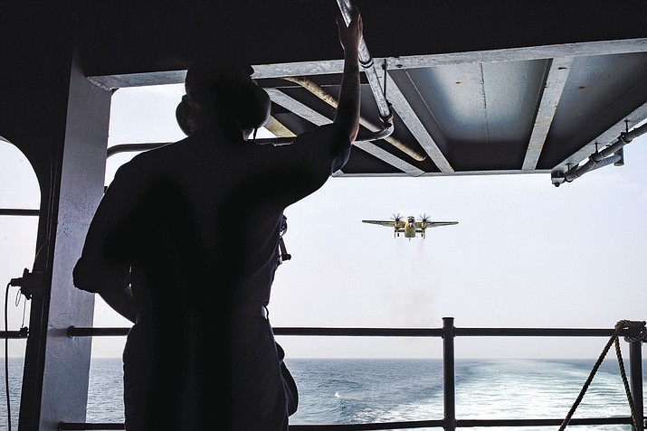 Seaman Jasmine Lutzi observes a C-2A Greyhound assigned to the Providers of Fleet Logistics Support Squadron (VRC) 30 as it approaches the flight deck of the aircraft carrier USS Theodore Roosevelt (CVN 71). Theodore Roosevelt and its carrier strike group are deployed to the U.S. 5th Fleet area of operations in support of maritime security operations to reassure allies and partners and preserve the freedom of navigation and the free flow of commerce in the region.