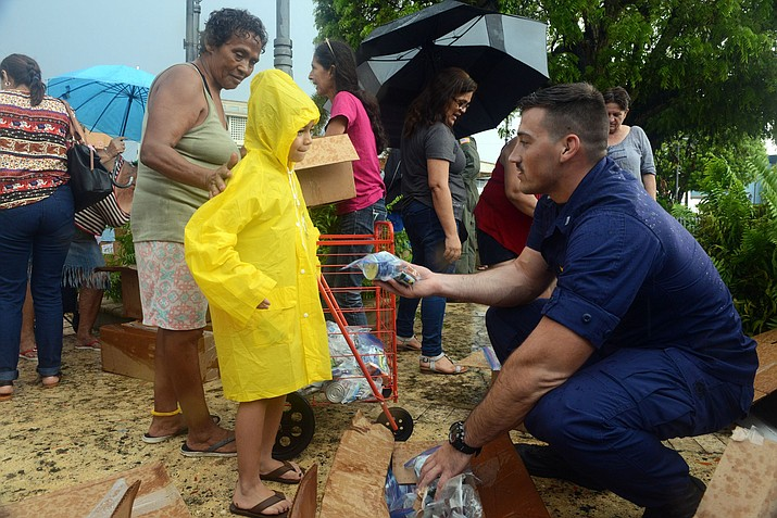 Lt. Lucas Taylor, a pilot at Coast Guard Air Station Borinquen, Puerto Rico, delivers food and water to a young girl in Moca, Puerto Rico, Oct. 9, 2017. The Coast Guard and partner agencies have been delivering Federal Emergency Management Agency supplies to people throughout Puerto Rico who have been affected by Hurricane Maria. U.S. Coast Guard photo by Petty Officer 3rd Class David Micallef.