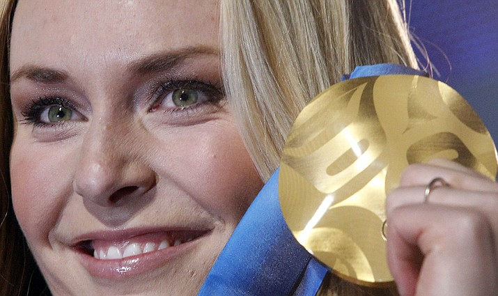 In this Feb. 17, 2010, file photo, Lindsey Vonn of the United States, shows the gold medal she won in the Women's downhill, during the medal ceremony at the Vancouver 2010 Olympics in Whistler, British Columbia. Vonn has some unfinished business on her agenda as she heads to the Pyeongchang Olympics. That includes trying to win more medals after missing the last Olympics because of a bad knee. (Luca Bruno/AP, File)