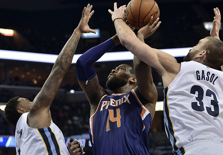 Phoenix Suns center Greg Monroe (14) shoots between Memphis Grizzlies center Marc Gasol (33) and forward Jarell Martin, left, in the second half of an NBA basketball game Monday, Jan. 29, 2018, in Memphis, Tenn. (Brandon Dill/AP)