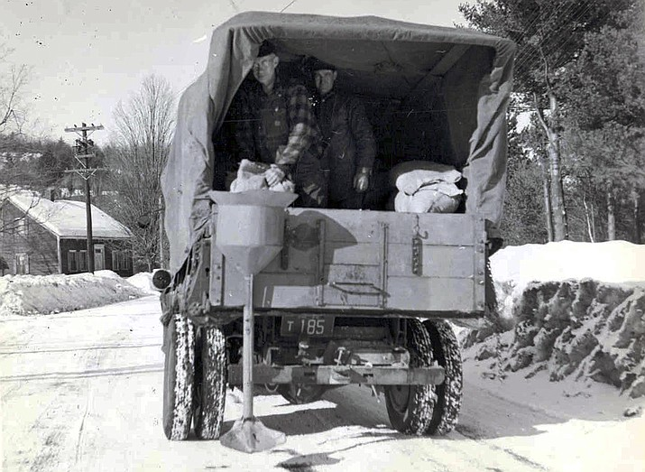 This circa 1940s photo released by the New Hampshire Department of Transportation archives shows salt being applied for anti-icing on a New Hampshire roadway. Some 20 million tons of salt is dispersed every year on American roads. Scientists in 2018 are starting to raise concerns about road salt's impact on the environment, especially drinking water, because lakes and streams near roads are showing elevated levels of sodium and chloride. (New Hampshire Department of Transportation)