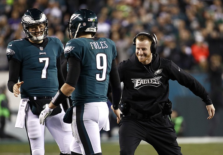 In this Sunday, Jan. 21, 2018, file photo, Philadelphia Eagles' Carson Wentz, right, congratulates Nick Foles (9) during the second half against the Minnesota Vikings in Philadelphia. Wentz, who is injured, watched both playoff games from the sideline, rooting hard for his teammates and enjoying their success without him. He'll be their No. 1 fan Sunday when they take on the New England Patriots and try to win the franchise's first NFL title since 1960. (Patrick Semansky/AP, File)