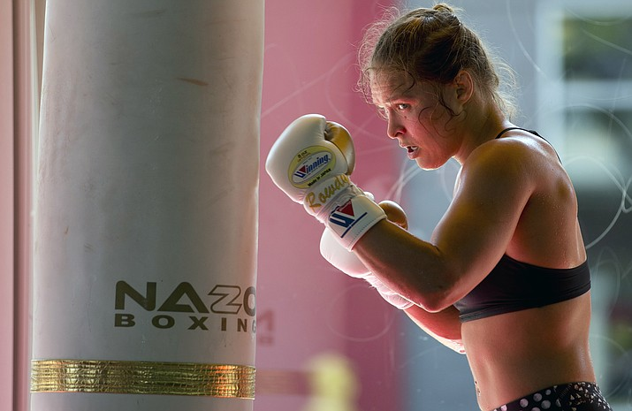 This July 15, 2015, file photo shows mixed martial arts fighter Ronda Rousey working out at Glendale Fighting Club in Glendale, Calif. The former UFC champion Rousey could soon make the move to WWE. She's met with WWE executives and has seemed excited about the possibility of becoming a wrestler. Rousey may not debut at one of WWE's signature events this weekend in Philadelphia because she's filming a movie in Colombia. (Jae C. Hong/AP, File)