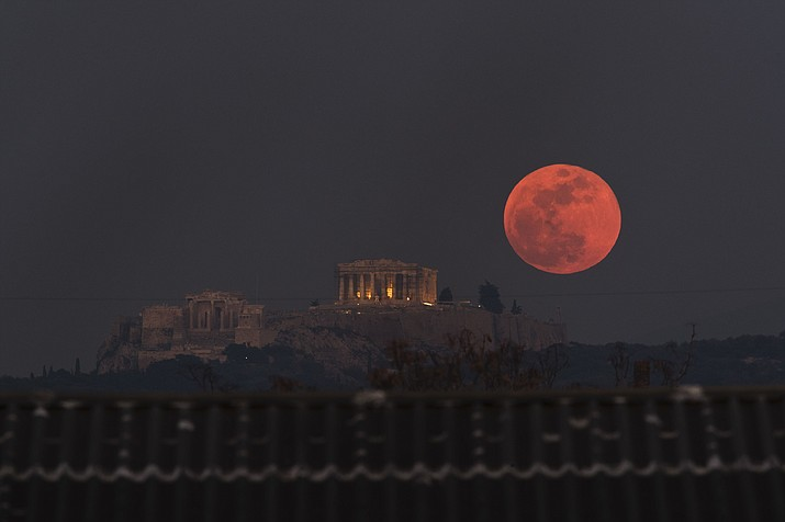 A super blue blood moon rises behind the 2,500-year-old Parthenon temple on the Acropolis of Athens, Greece, on Wednesday, Jan. 31. It was a super moon (it's closest point to earth, a blue moon (second full moon of a month) and a blood moon, which is lunar eclipse that creates the red color. (Petros Giannakouris/AP)