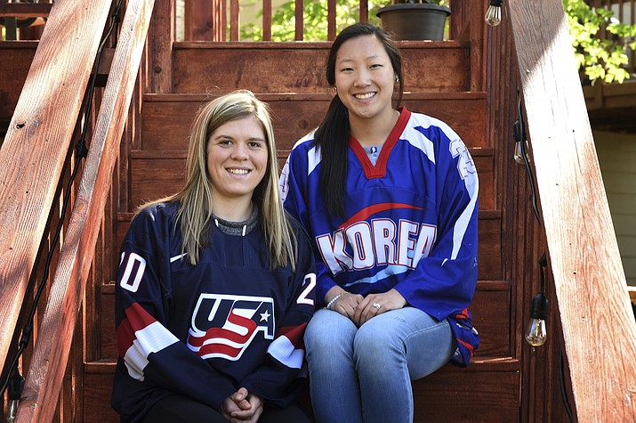 FILE - In this May 11, 2017, file photo, sisters Hannah, left, and Marissa Brandt, pose at their family's home in Vadnais Heights. Minn. Marissa, a native Korean who was adopted as an infant by parents in Minnesota, and her sister Hannah will both be playing in the upcoming Winter Olympics in women's hockey. Marissa for South Korea and Hannah for the U.S. (Scott Takushi/Pioneer Press via AP)