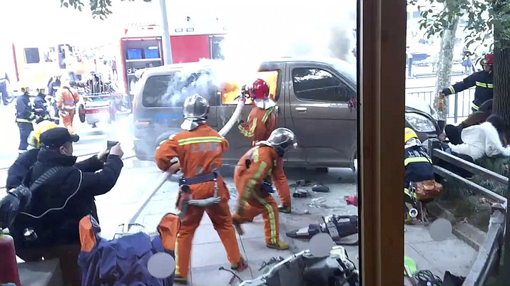 In this image taken from cellphone video provided to the Associated Press, firefighters put out a blaze after a minivan carrying gas tanks plowed into pedestrians along a street in Shanghai, Friday, Feb. 2, 2018. A minivan plowed into pedestrians on a sidewalk in downtown Shanghai on Friday, sending more than a dozen people to hospitals. (AP Photo)