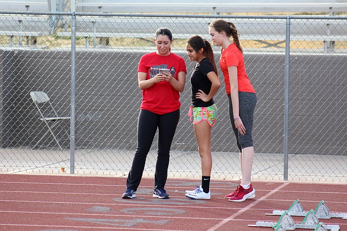 New Mingus head track coach Molly Westcott goes over recordings of Marauders' starts on her phone with Josey Valenzuela (left) and  Olivia Grasso (right). Westcott starred at Mingus Union in high school and now teaches English there too. (VVN/James Kelley)