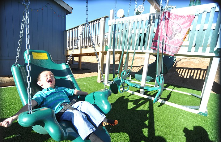 Sean Pfister enjoys his new swingset that he received from the Make a Wish Foundation and the Yavapai County Contractors Association.  (Les Stukenberg/Courier, file)