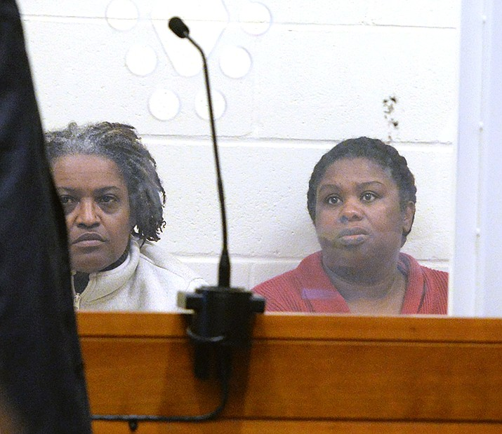Rachel Hilaire and Peggy LaBossiere appear at Brockton District Court on on Wednesday, Feb. 1, 2018 in Bridgewater, Mass. The two sisters tied down and burned a 5-year-old girl, permanently disfiguring her, in a voodoo ritual meant to rid her of a demon causing her to misbehave, police said. The women also threatened to cut off the head of the unnamed girl's 8-year-old brother with a machete, authorities said. LaBossiere, 51, and Hilaire, 40, denied injuring the girl and threatening the boy and pleaded not guilty Monday, Jan. 29, to mayhem, assault and other charges. (Marc Vasconcellos/Enterprisenews.com via AP)
