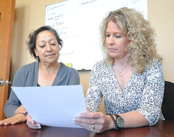 Yavapai County Human Resources manager Esther Hunt and Director of Human Resources and Risk Management Wendy Ross show one of the initial steps when investigating a sexual harrasment complaint is to read the initial claim report to determine what steps to take from there. (Les Stukenberg/Courier)