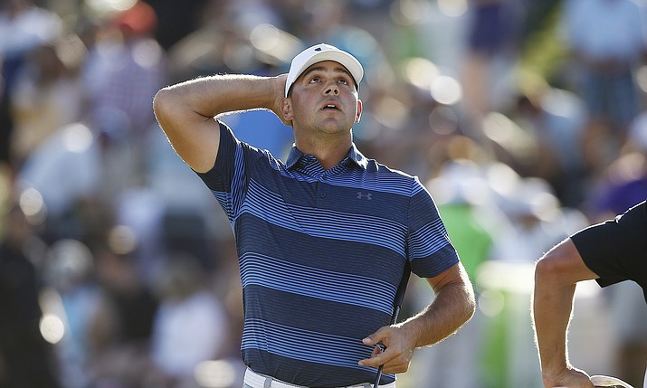 Gary Woodland pauses on the 18th green after his win in a one-hole playoff against Chez Reavie for the final round of the Waste Management Phoenix Open golf tournament Sunday, Feb. 4, 2018, in Scottsdale, Ariz. (Ross D. Franklin/AP)