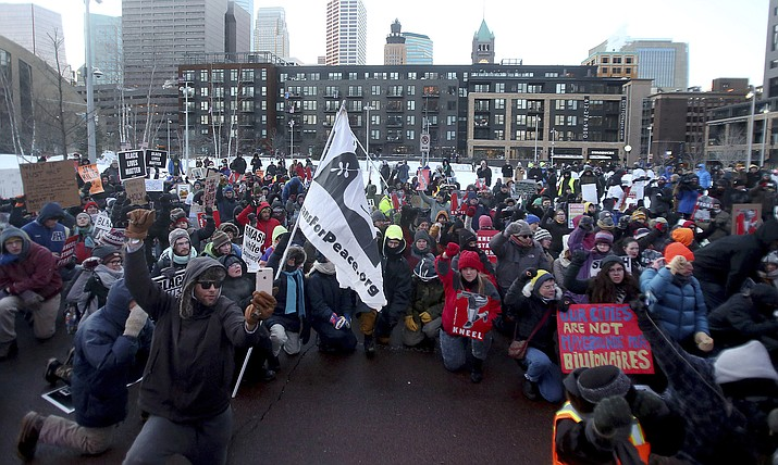 Hundreds of protesters take a knee outside U.S. Bank Stadium, outside the Super Bowl as an Anti-Racist Anti-Corporate rally joined with Take a Knee Nation, Sunday, Feb. 4, 2018, in Minneapolis, Minn. Activists in Minnesota are using the spectacle of the Super Bowl to speak out against police brutality, racism, corporate greed and other issues. (David Joles/Star Tribune via AP)
