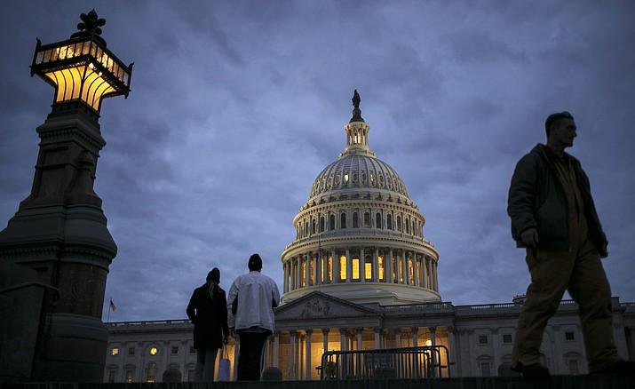 In this Jan. 21, 2018, file photo, lights illuminate the U.S. Capitol on the second day of the federal shutdown as lawmakers negotiated behind closed doors in Washington. (AP Photo/J. Scott Applewhite, File)