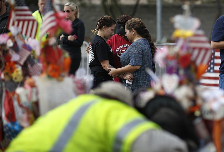 Nikki Alirez, from left, Anna Martinez and Tina Lugo pray as workers remove a makeshift memorial honoring the victims of the Oct. 1 mass shooting in Las Vegas. The memorial will be moved to a museum where it will become part of a permanent collection.  (John Locher/AP)