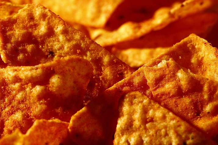 "FILE- This Sept. 26, 2014, file photo shows Nacho Cheese flavored Doritos in Philadelphia. Don't expect to see ""lady Doritos"" on store shelves. The company that makes the cheesy chips said Tuesday, Feb. 6, 2018, that it's not developing a line of Doritos designed specifically for women, despite widespread online speculation that it was. (AP Photo/Matt Rourke, File)"