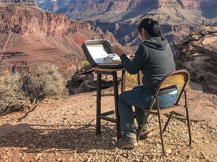 A hiker stops to leave a message on the typewriter stationed at Plateau Point.