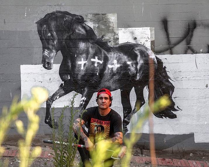 Cheyenne Randall with his mural 'Horse'. Randall is creating murals at the Heard Museum campus in Phoenix Feb. 2 to 8 before traveling to northern Arizona.